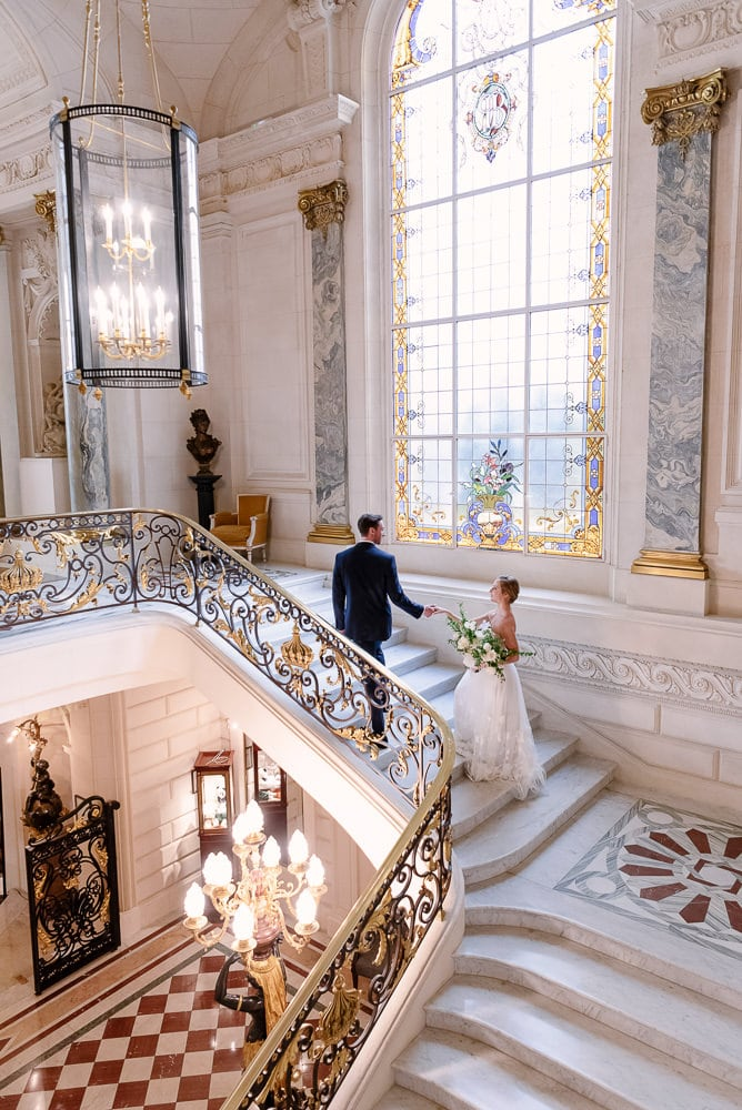 Paris wedding 2020 - Bride and groom walking up the iconic stairs of the Shangri la