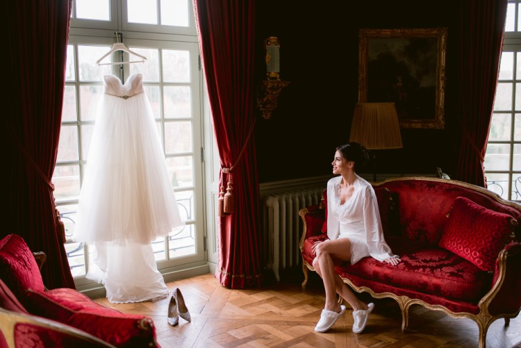 Bride looking at her wedding dress before getting ready for ceremony in Chateau de Villette