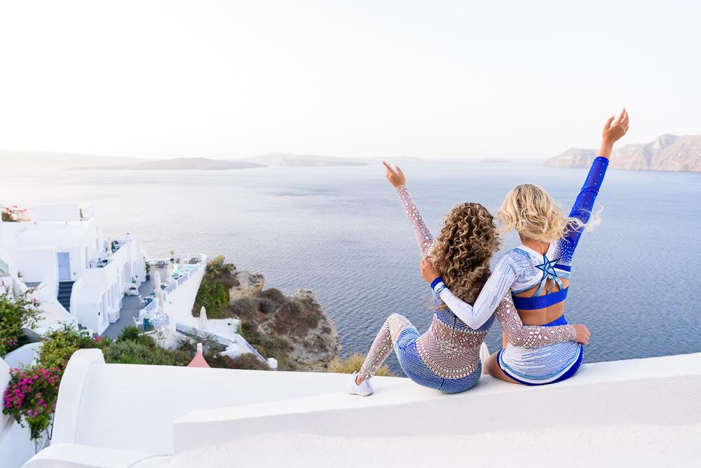 Girls hugging in cheerleading apparel and waving in Santorini island