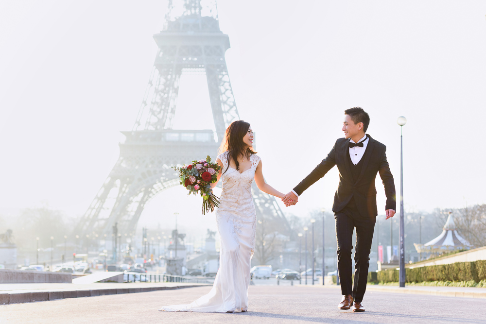 Asian bride and groom running hand in hand near Trocadero fountains
