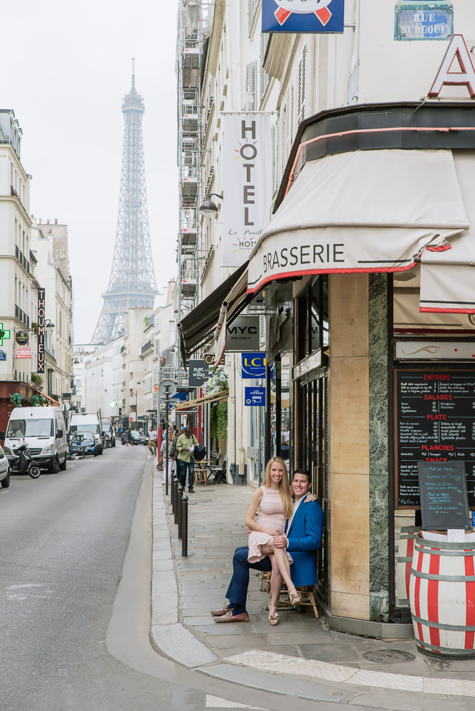 Couple sitting in a cafe on a street with eiffel tower view