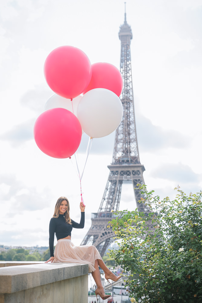 Girl with red and white balloons posing for portraits at the Eiffel Tower