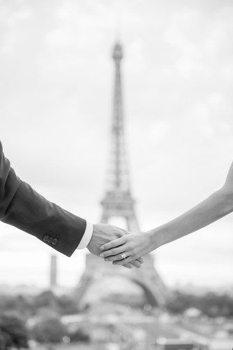 Newly engaged couple holding hands in front of the Eiffel Tower for their engagement pics