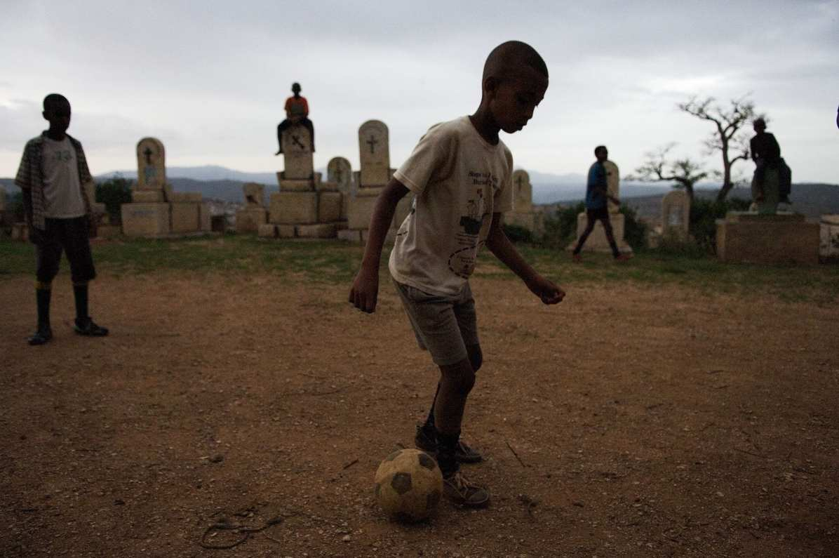 P79. Boys play soccer at a cemetery in Harare, Ethiopia. Almost 90% of the total number of children living with HIV lives in sub-Saharan Africa and fewer than one in ten of those children are being reached by basic support services.