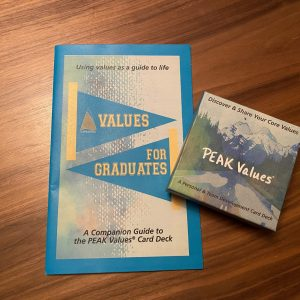 PEAK Values Card Deck Box displayed with the Values for Graduates booklet on a wood grain background
