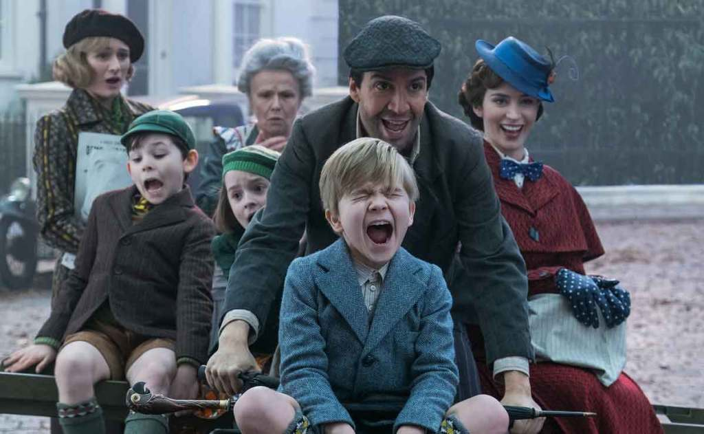Cast of Mary Poppins returns frolicking on a bike.