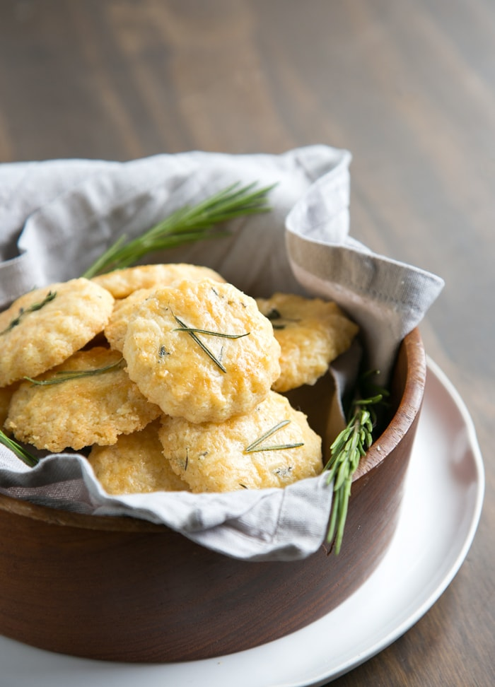 parmesan cookies in a large wooden bowl covered with grey napkin, white plate beneath and wood table in the background