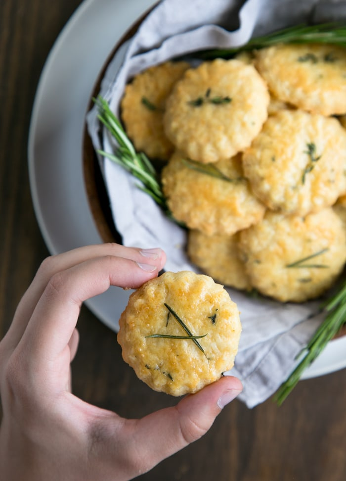 hand holding a parmesan cookies, plate with parmesan cookies and rosemary sprigs in the background