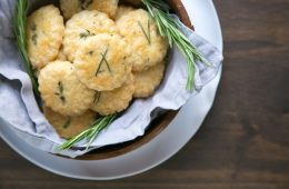 parmesan cookies and rosemary sprigs in a wood bowl covered with grey napkin, white plate beneath on wood table