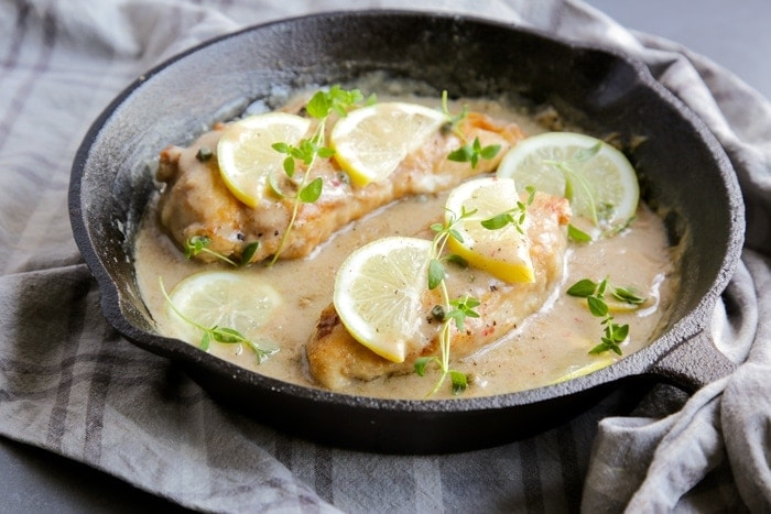 Chicken piccata in a large skillet with sauce, topped with lemon slices and thyme leaves