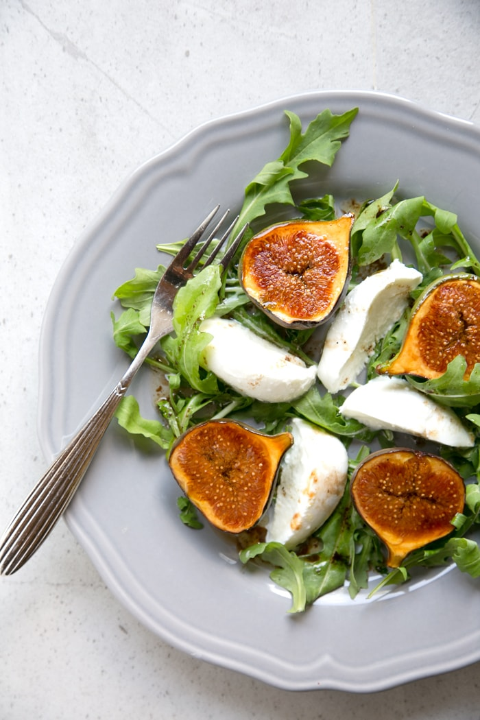 fig and mozzarella salad with arugula on grey plate with fork on th left and knife on the right, two fresh figs on the side over grey napkin