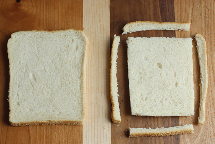 fried mozzarella sandwich preparation, step one: two white bread slices on wood board, one with the crust cut off