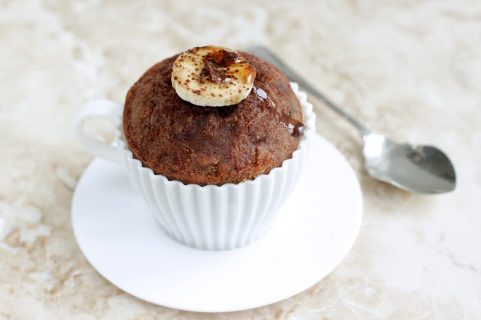 gluten-free banana muffins in a tea cup-shaped mould, with teaspoon on the side