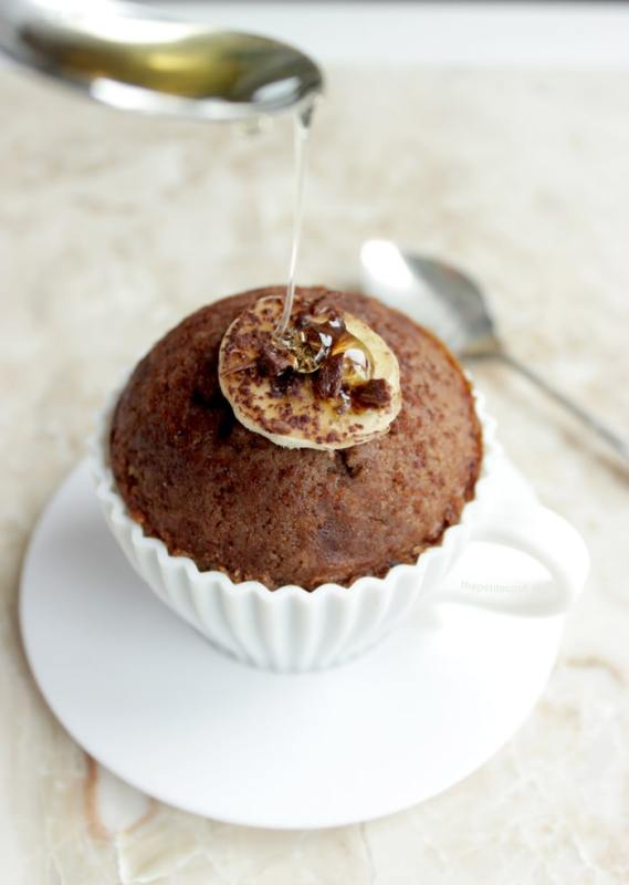 Gluten-free banana muffins in a tea cup-shaped mould with honey spooned from above.