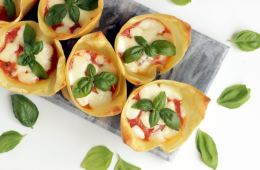 flat lay image of italian lasagna cups on grey board, basil leaves scattered over the white background