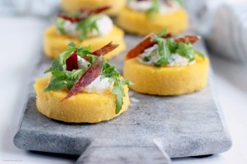 polenta crostini topped with jamon, ricotta and rocket leaves