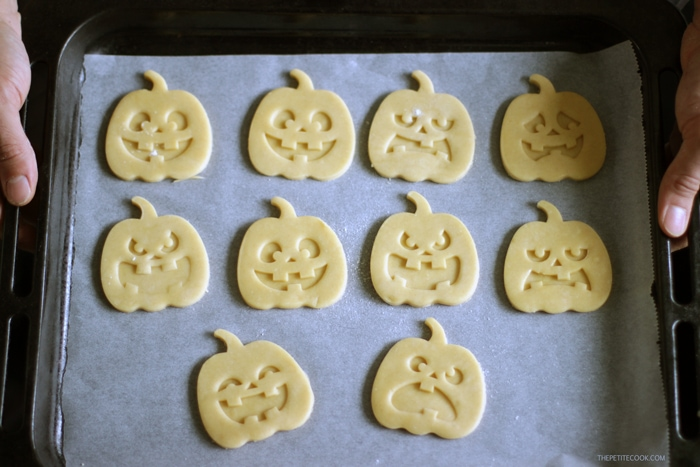 pumpkin shaped halloween italian shortbread cookies raw on baking tray covered with parchment paper held by two hands