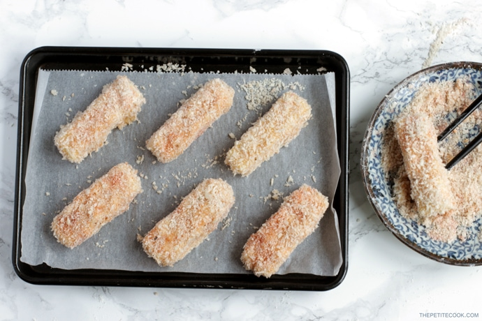 recipe process step 3: mozzarella sticks dipped in flour, eggs and panko breadcrumbs then arranged on a baking tray covered with parchment paper
