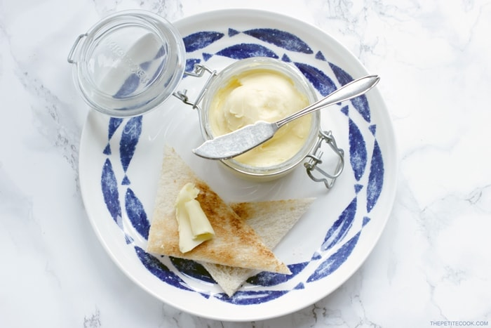 homemade butter with a2 milk in a jar with a knife over it, bread toasted with butter on top on a large white and blue plate