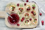 brie and cranberry cups on a wood board, served with homemade cranberry sauce.