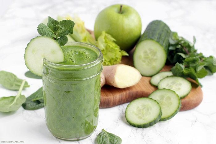 green juice in a glass, next to a wood board with fresh ginger, celery stalks, cucumber and cucumber slices, green apple and spinach leaves
