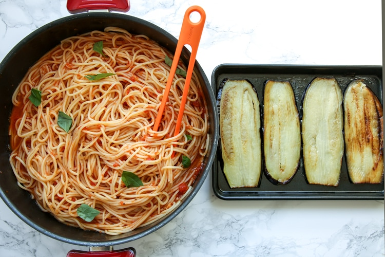 Eggplant spaghetti sandwichesprocess: pot wioth spaghetti and tomato sauce next to baking tray with cooked eggplant slices