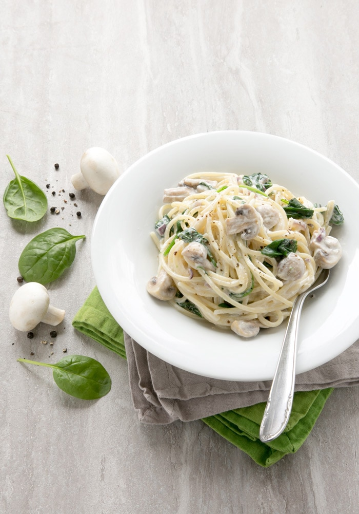 This Mushroom and Spinach Spaghetti recipe has the most amazing and easy creamy sauce - Vegetarian and packed with nutrients, it comes together in just 15 min! Recipe from thepetitecook.com