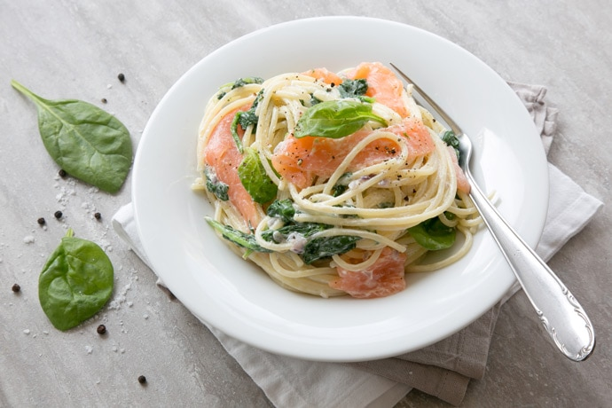 This Salmon, Mushroom and Spinach Spaghetti recipe has the most amazing and easy creamy sauce - Packed with nutrients, it comes together in just 15 min! Recipe from thepetitecook.com