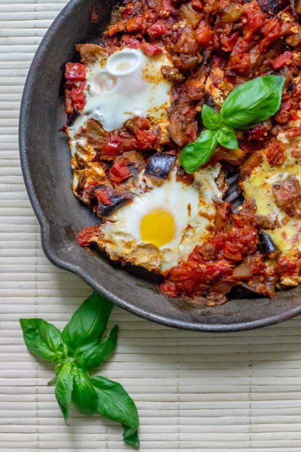 vegetarian eggplant shakshuka in a cast iron skillet next to basil leaves