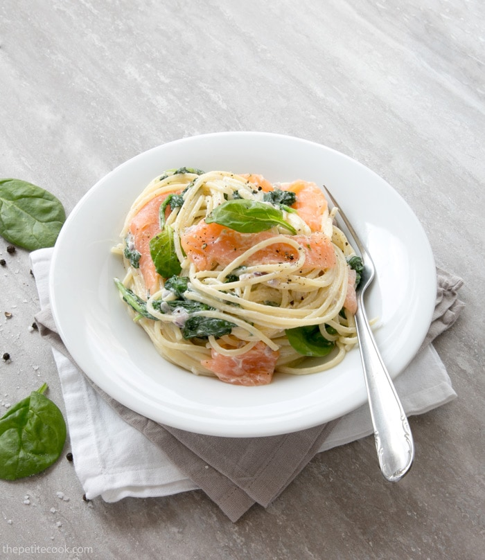 Spaghetti with Salmon and Spinach in a white plate with a fork, over a grey and a white napkins, spinach leaves pepper and salt scattered next to the plate