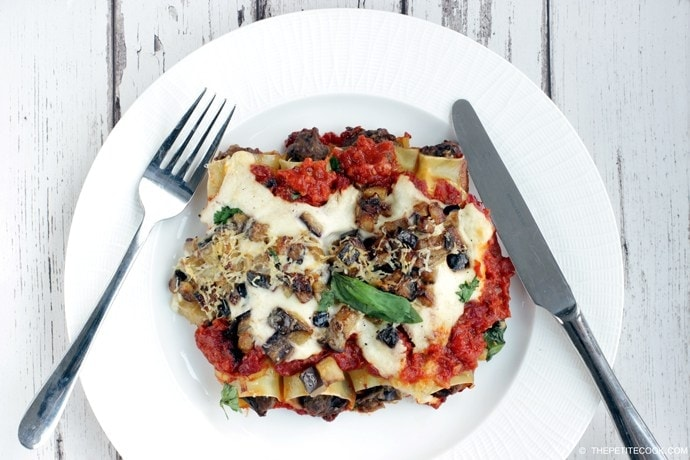 vegetarian eggplant recipes collection, image featuring roasted eggplant cannelloni on a white plate with fork and knife on the sides