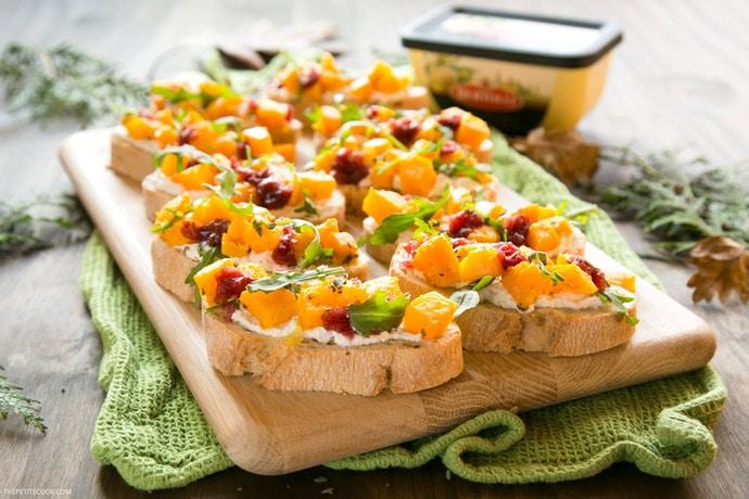 roasted pumpkin bruschetta on wood board with Bertolli spread in the background