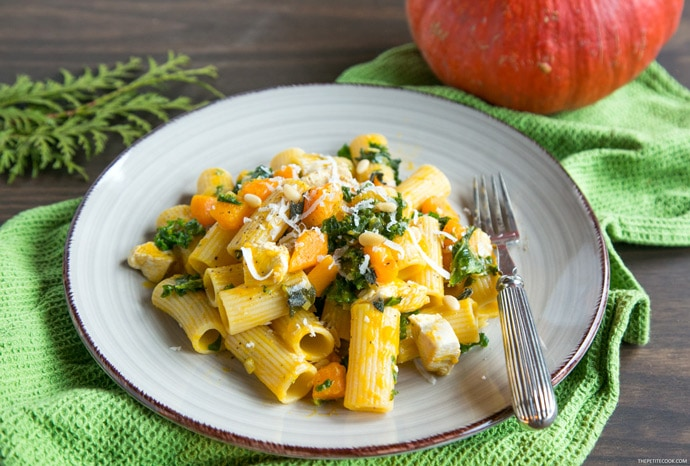 pasta with pumpkin kale and chicken on a plate with a fork and a pumpkin on the background