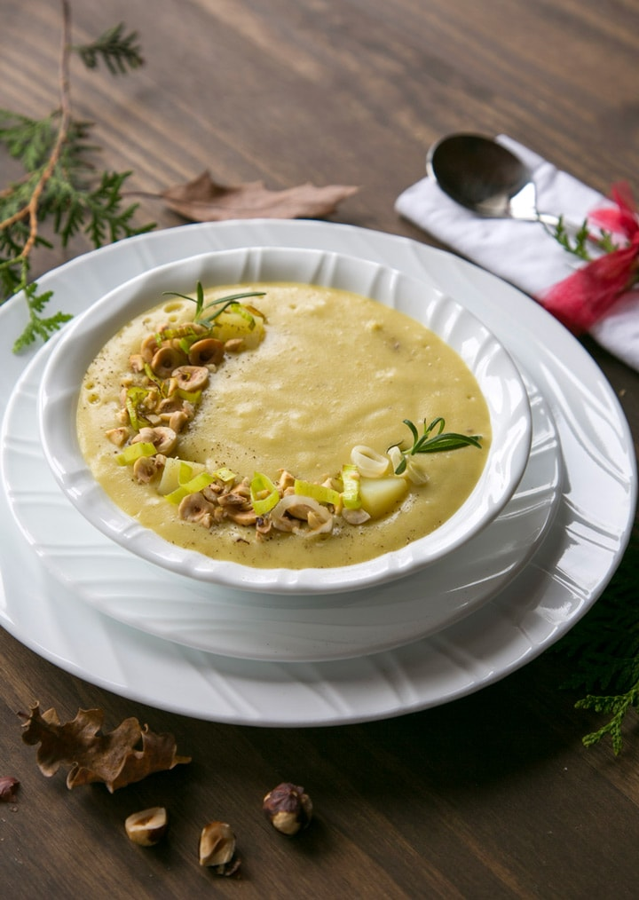 Leek and Potato soup in white bowl over two white plates, spoon on the side over a white napkin. brown and green leaves, and toasted hazelnuts scattered over the wood table