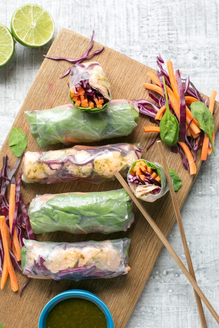 Vietnamese summer rolls on a wood board with halved lime, chopsticks and a small blue pot with cilantro dipping sauce.