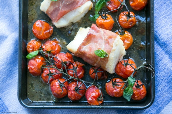 Make dinner time easy with this Prosciutto Wrapped Cod with Roasted Tomatoes - A one-tray easy italian-style meal, gluten-free, dairy-free and ready in just 20 min! Recipe by The Petite Cook - www.thepetitecook.com