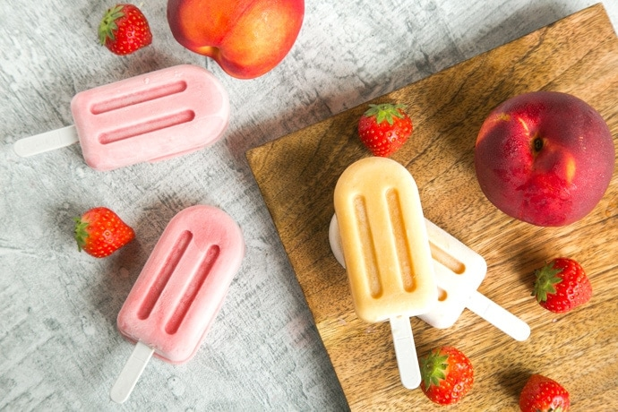 Nectarine and Strawberry Smoothie Popsicles, two on wood plate next to a nextarine and strawberries, two on grey background next to 2 strawberries and another nectarine