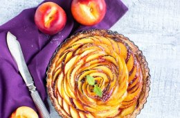 nectarine tart over a purple napkin, two nectarines on the top, half nectarine and a knife on the bottom,