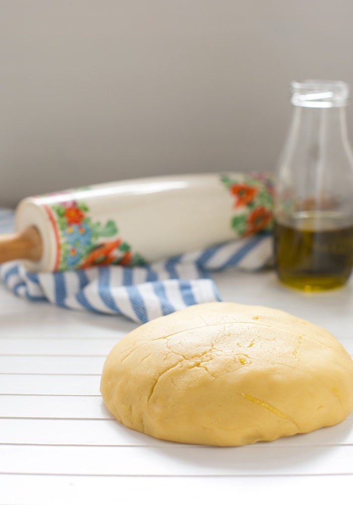 olive oil shortcrust pastry on a white wood board, olive oil in a glass bottle and rolling pin on a striped kitchen cloth in the background