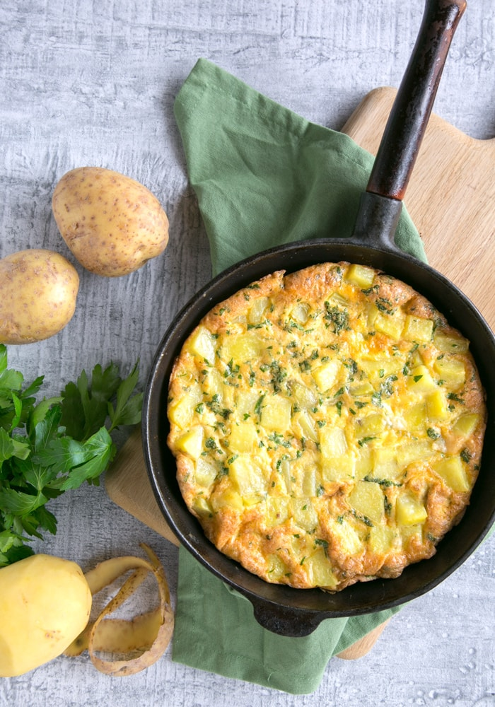 Classic Italian Potato Frittata in a cast iron skillet over a wood board with green napkin, potatoes and parsley on the background.