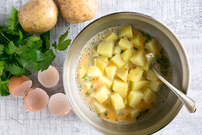 whisked eggs, parsley and chopped potatoes in a large bowl, next to egg shells parsley and potatoes