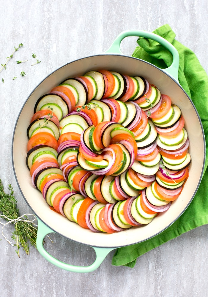 Raw Easy Ratatouille in a large green cast iron shallow pan, bunch of thyme sprigs on the left side and a green napkin on the top right side.