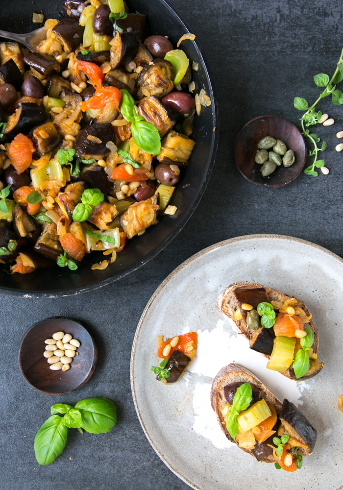 vegetarian eggpkant caponata in a skillet, next to a small pot of capers, and a small pot of pine nuts, next to a grey plate with two slices of bread topped with caponata