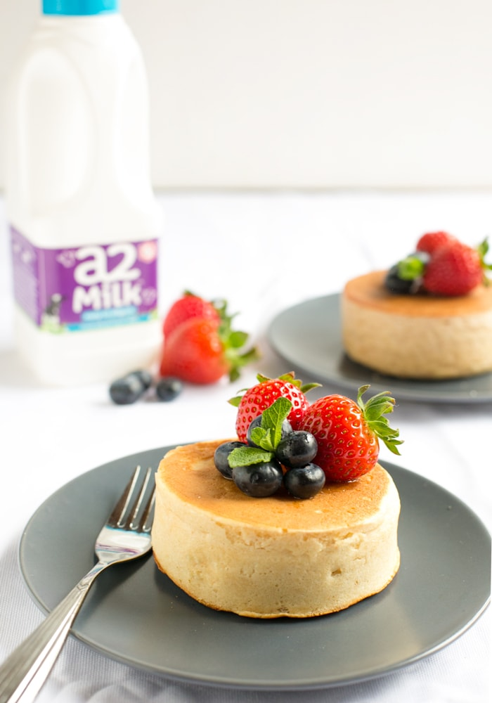 Japanese pancake topped with strawberries and blueberries and fork next to it, on grey plate and white tablecloth, a2 Milk bottle and another japanese pancake in the background