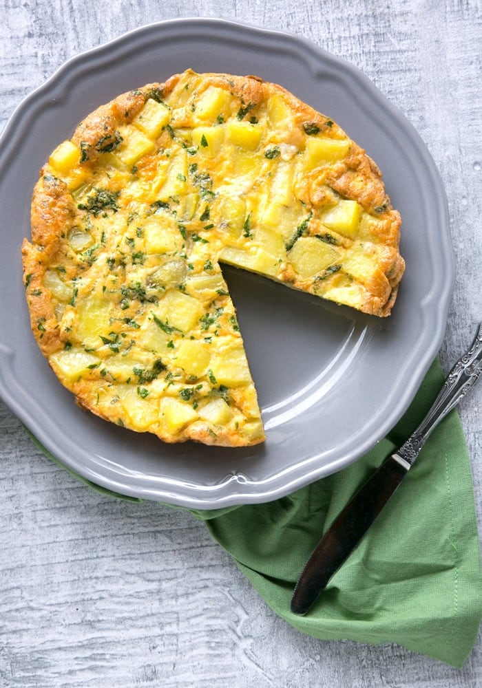 Classic Italian Potato Frittata on a grey serving plate and knife on green napkin on the side.