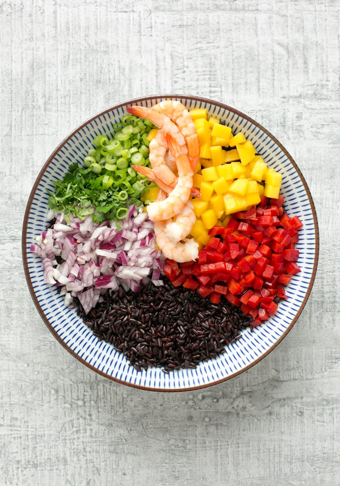 venere black rice salad with shrimps and mango, pepper, red onion, spring onion, shrimps in a bowl