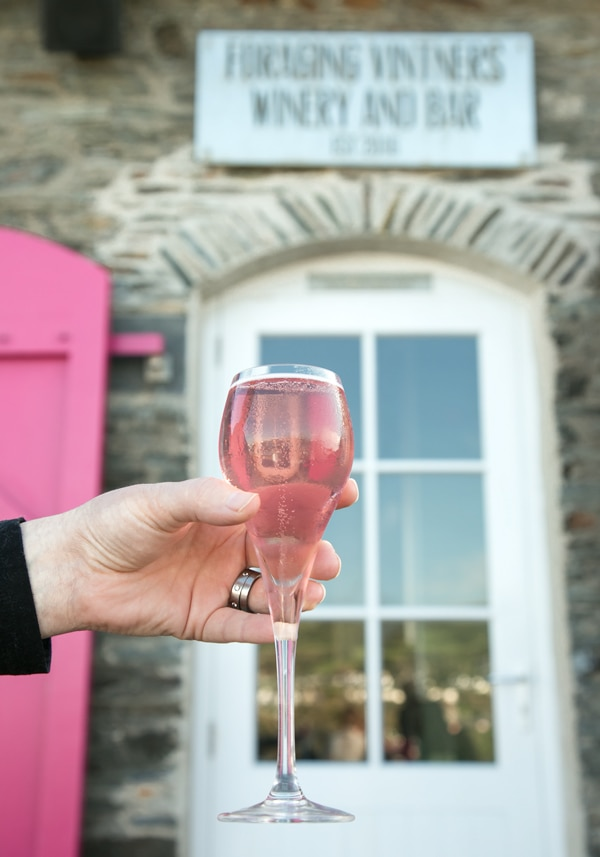 rhubarb wine in prosecco glass, winery entrance in the background