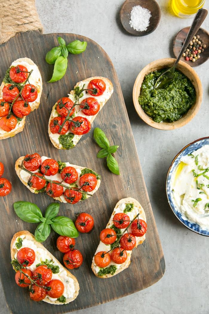 confit tomato bruschetta with ricotta and basil pesto over wood board