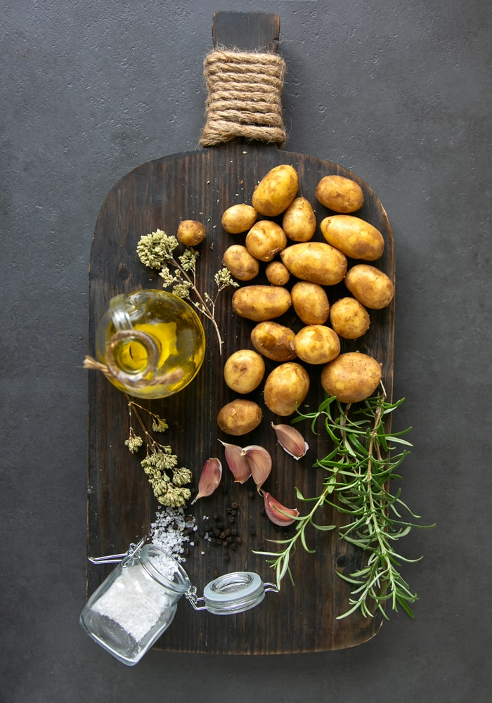 dark wood board, on top potatoes, olive oil bottle, rosemary sprigs, garlic, oregano sprigs and sea salt in small jar
