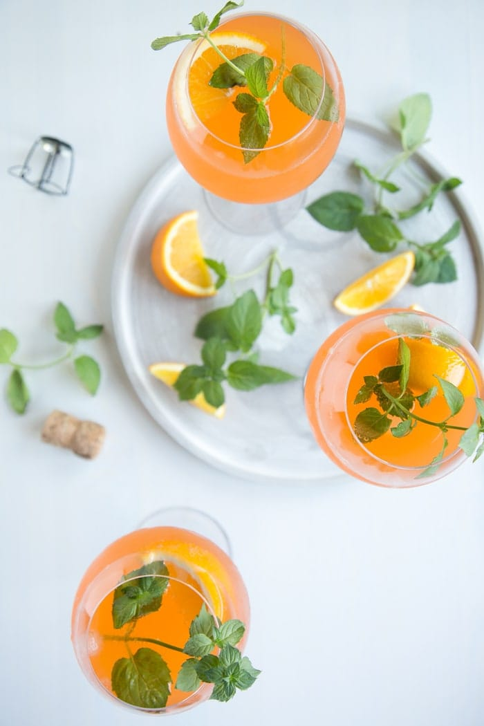 orange spritz cocktail in three wine glasses decorated with orange slices and mint leaves